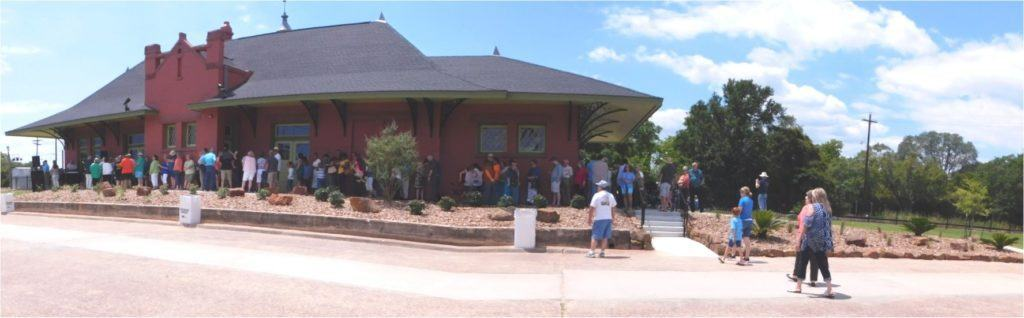 Orange Train Depot Museum Image of people around the depot